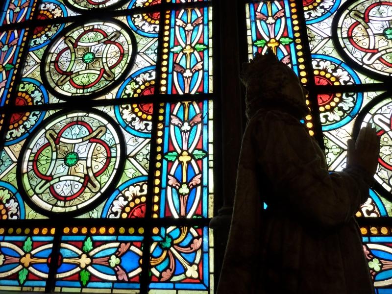 Catherine de Medici statue silhouette in front of stain glass, Saint Denis Basillica, Paris