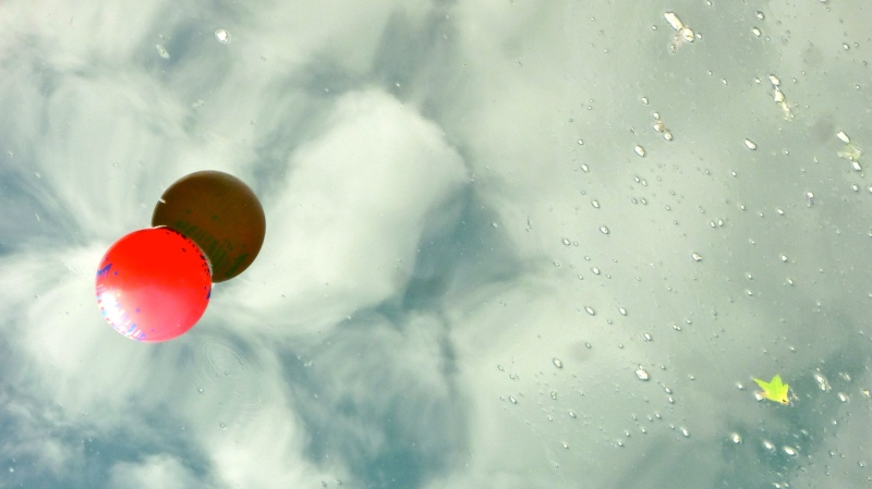 Red ball on reflective water, cloud reflections
