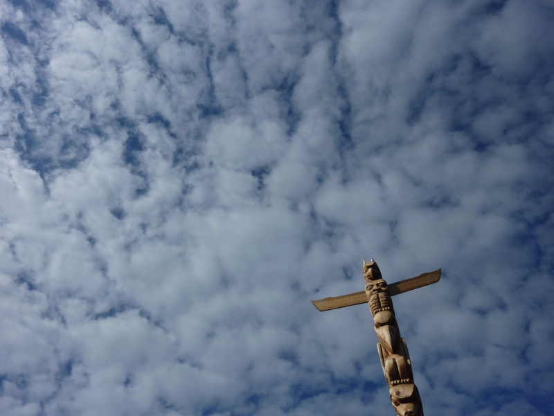 BC totem pole against blue sky with clouds, Stanley Park