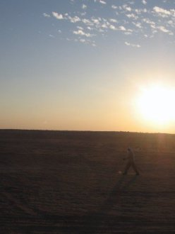 Bedouin walks past sunset in Sahara desert