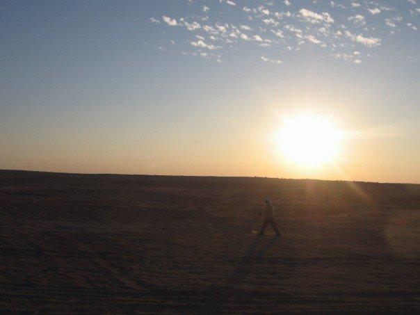 Bedouin walks past sunset in Sahara desert