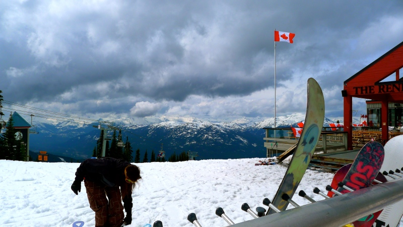 Snowboarder on to of Blackcomb Mountain, Whistler BC, Canada flag