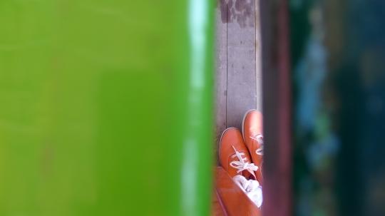 Orange keds shoes under green tables