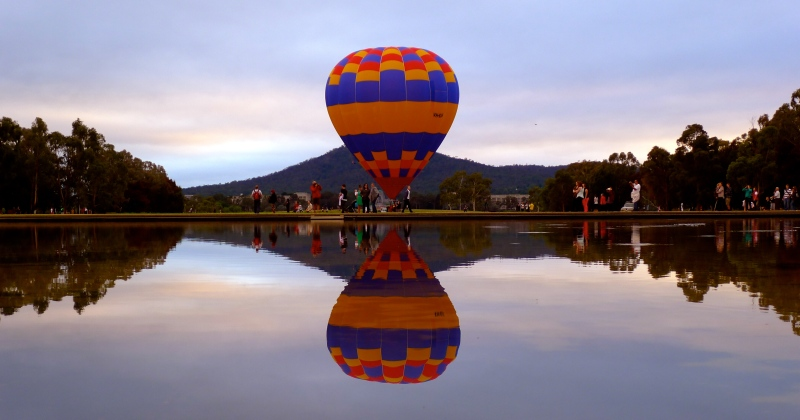 hot air balloon preparing to take off reflection water