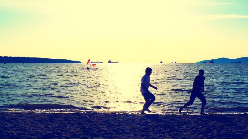 Men running on beach, English Bay, Vancouver